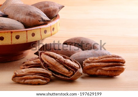 Close up pecan nuts with ceramic bowl on a wooden background - stock photo