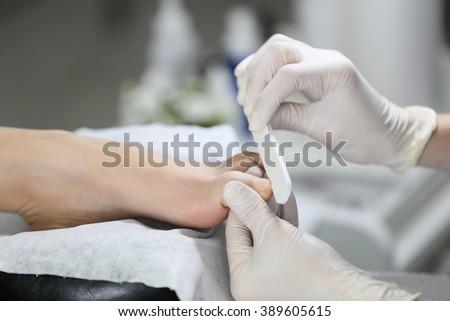 Close-up pedicure process of the big toe in spa salon. Professional work pedicure masters. - stock photo