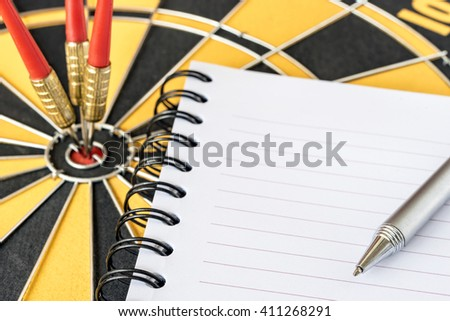 Close up pen on recycle notebook with three darts target on bullseye background, Goals target marketing success business investment financial strategy concept, abstract background - stock photo