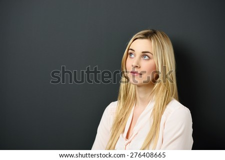 Close up Pensive Young Blond Woman Looking Up Seriously Against Black Wall Background with Copy Space. - stock photo