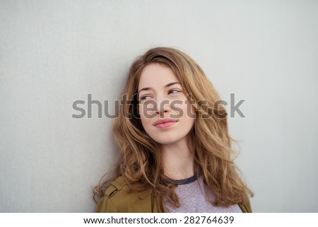 Close up Pensive Young Brown-Haired Woman Leaning on the White Wall While Looking Into Distance. - stock photo