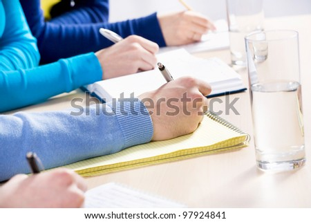Close-up people's hands writing something during lecture - stock photo
