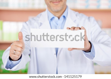 Close up pharmacist showing thumbs up and white envelope - stock photo