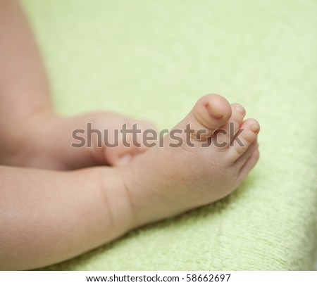 close up photo of a baby feet on green background - stock photo