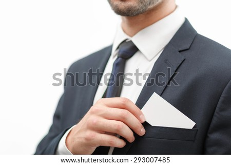 Close up photo of a bearded man wearing a formal black suit holding a card with copy space in the small pocket at the blazer, isolated on white background - stock photo