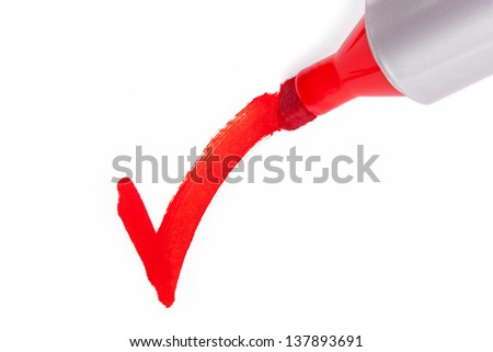 Close-up photo of a big red felt tip marker pen writing a tick on white paper - stock photo