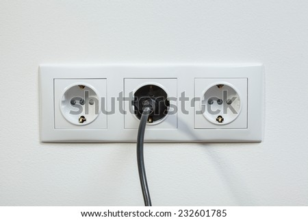 Close up photo of a black power plug plugged in a triple electric socket  - stock photo
