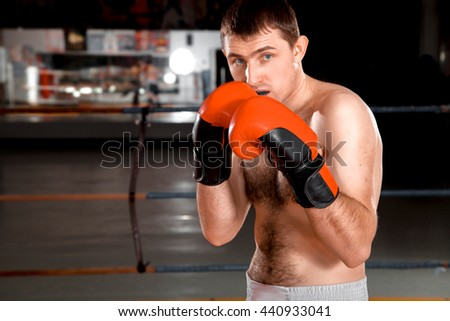 Close-up photo of a boxer in red gloves on the ring