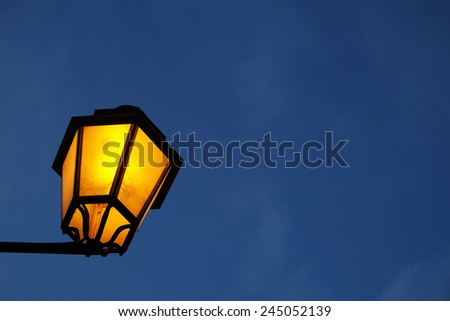 Close up photo of a classic lit street lamp post, against clear sky, night time. - stock photo