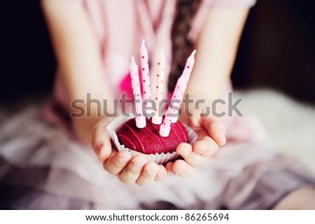 Close-up photo of a cupcake with five candles in child's hands, focus on a cupcake with softening filter use - stock photo