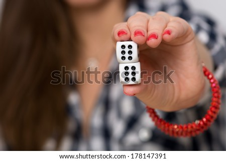 Close up photo of a female hand holding two dices and showing double six - stock photo