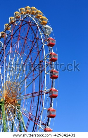 Close-up photo of a ferris wheel under a clear blue sky. - stock photo