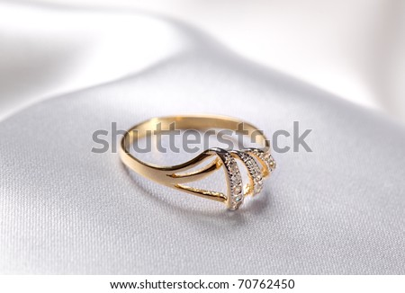 Close up photo of a golden  ring at white textile background - stock photo