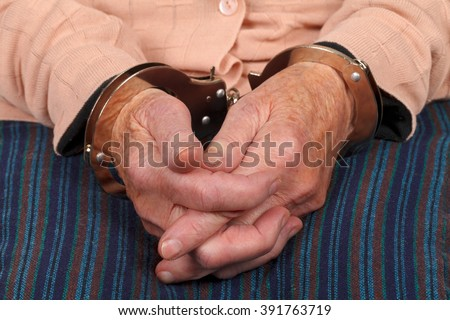 Close up photo of a handcuffed elderly woman - stock photo