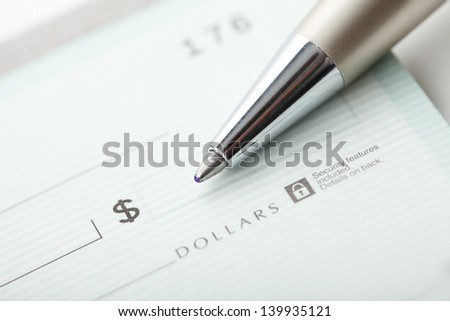 Close up photo of a pen and blank dollar check. Shallow focus