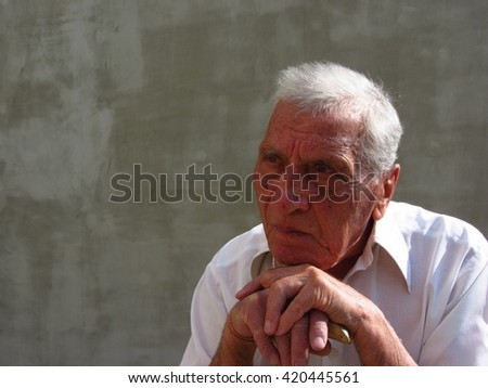 Close up photo of a retired old man in his eighties, leaning on his cane and thinking about the future and the past.