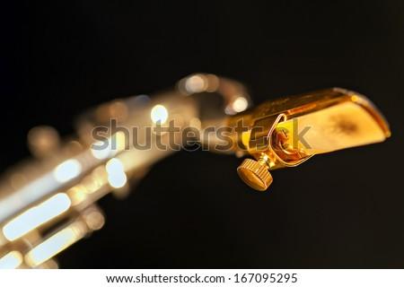 Close up photo of a shiny golden saxophone mouthpiece - stock photo