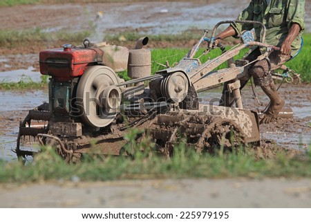 Close up photo of a tractor working in the paddy field in Vietnam. - stock photo