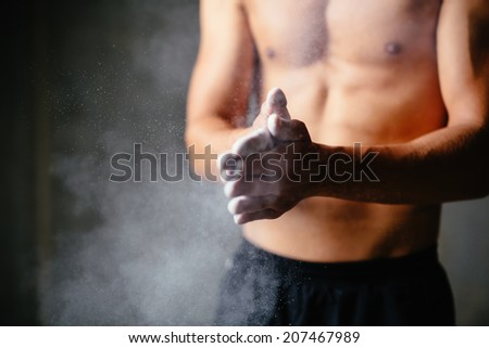Close-up photo of a wall climber putting talc on his palms