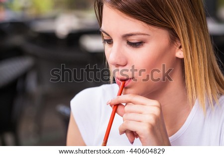close up photo of a woman, she is drinking refreshment with a straw, in a restaurant - stock photo