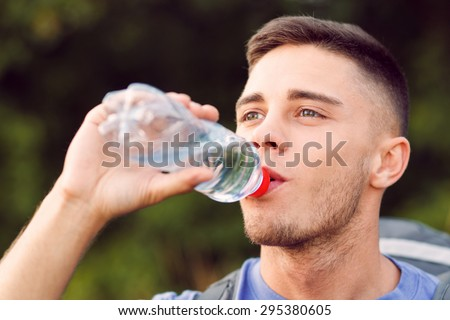 Close up photo of a young handsome tourist wearing blue t-short and backpack standing, drinking water from the bottle - stock photo