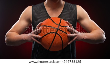 Close up photo of a young male basketball player gripping the ball tightly on red background - stock photo