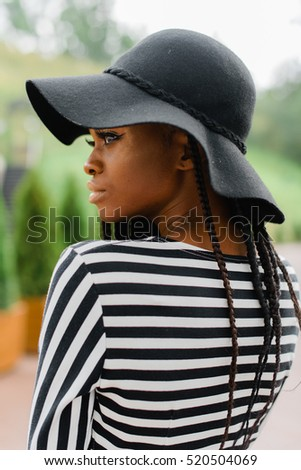 Close up photo of attractive american girl. Female looking at somewhere. Model in black hat.