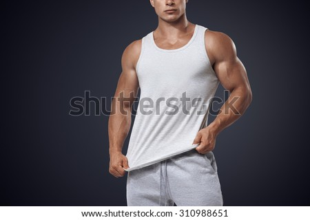 Close up photo of attractive bodybuilder wearing blank white sleeveless t-shirt, vest