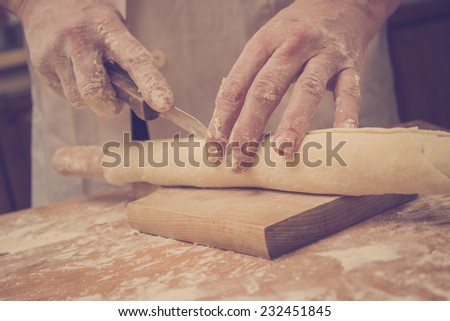 Close up photo of baker making noodles. Cutting the dough on the roller pin. - stock photo