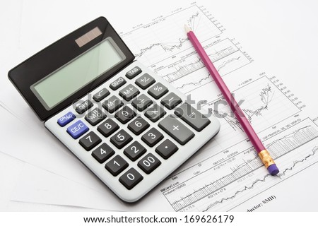Close-up photo of business objects: calculator, pen, diagrams