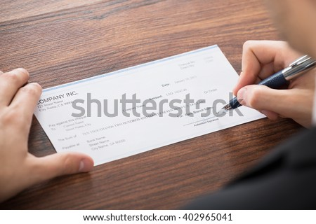 Close-up Photo Of Businessman Filling Blank Cheque - stock photo