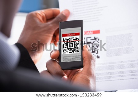 Close-up Photo Of Businessman Hand Scanning Code - stock photo