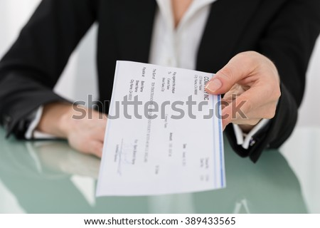 Close-up Photo Of Businesswoman Hand Giving Cheque - stock photo