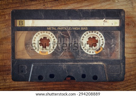close up photo of cassette tape over wooden table . top view.  - stock photo