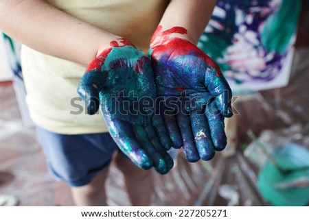 close up photo of childish hands in paints  - stock photo