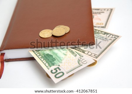 close up photo of dollars and small change in leather notebook - stock photo