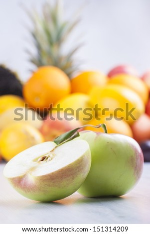 Close up photo of edible fruits - a apples with other full colors fruits in the background on a solid  bright blue wooden table
