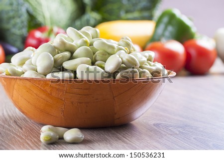 Close up photo of edible vegetables - a broad bean with some vegetables in the background on a solid  brown wooden table - stock photo