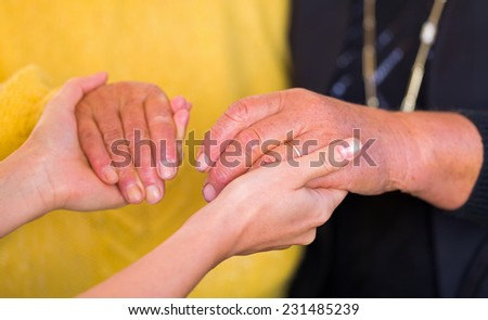 Close up photo of elderly women hand hold by young carer hands - stock photo