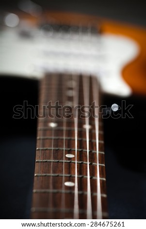 Close-up photo of electric guitar, very shallow depth of field