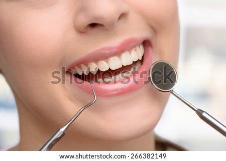 Close up photo of female patient with open mouth receiving dental inspection at dentist office - stock photo