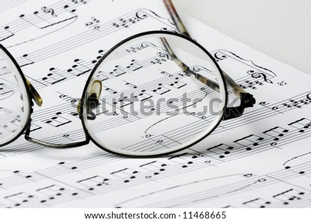 Close up photo of glasses on sheet music - stock photo