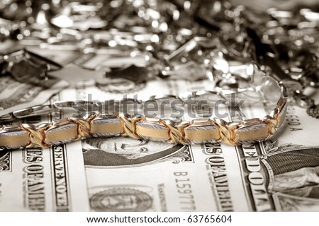 Close up photo of golden bracelet  and other jewelry at money background - stock photo