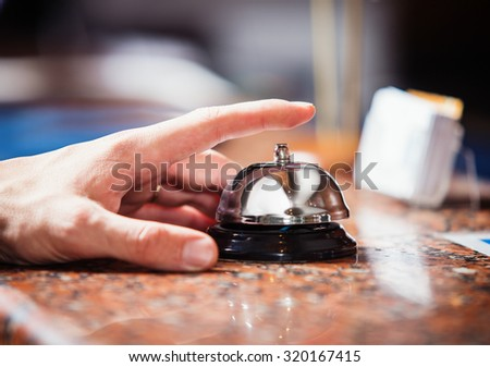 Close up photo of hand  ringing a hotel reception service bell to attract attention