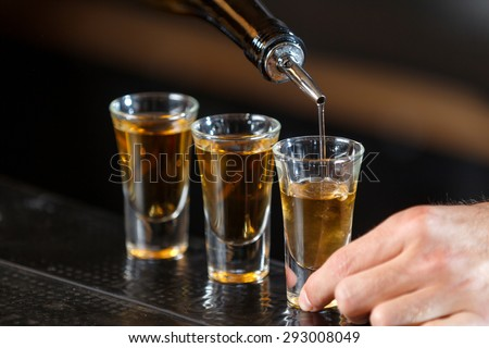 Close up photo of hands of a bartender pouring some drink into shot glasses on a wooden counter - stock photo