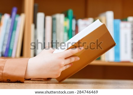 Close up photo of hands on a woman making holding a book sitting at the table in a library, bookshelves on a background