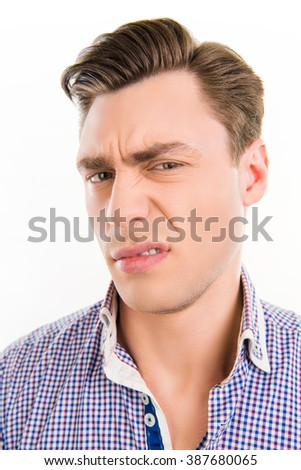 Close up photo of handsome man with unhappy grimace on his face