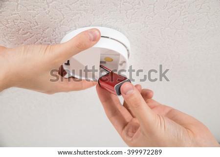 Close-up Photo Of Handyman Repairing Smoke Detector - stock photo