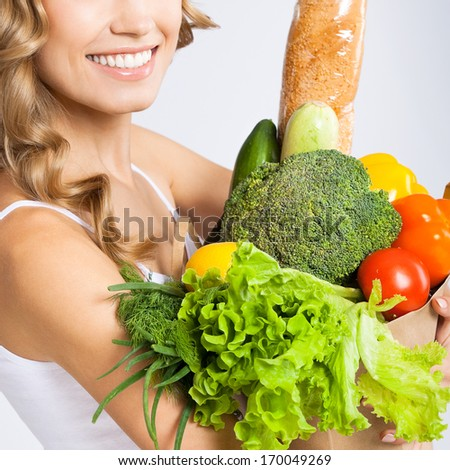 Close up photo of happy smiling young beautiful woman holding grocery shopping bag with healthy vegetarian raw food, over gray background