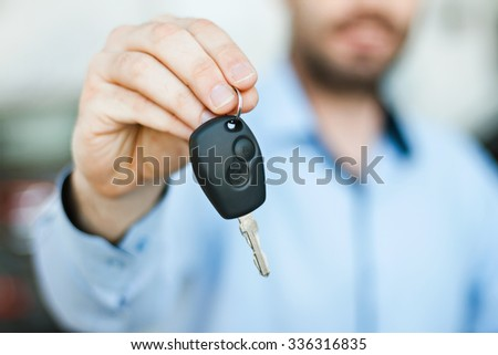 Close up photo of happy young man showing key to his new car. Concept for car rental. Focus on key